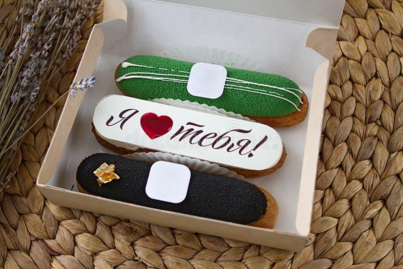 Três eclairs doces bonitos apetitosos do desenhista com enchimentos diferentes e o ` do ` da inscrição eu te amo em uma caixa de  fotos de stock royalty free