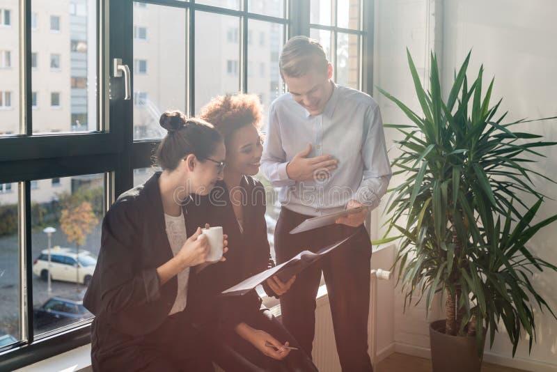 Três empregados alegres novos que sorriem em um escritório moderno fotos de stock royalty free