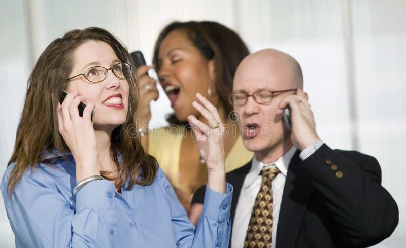 Três empresários em telefones de pilha imagem de stock royalty free