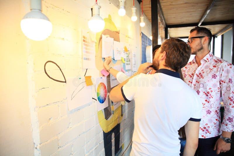 Três empresários que discutem e que planeiam o conceito Parte dianteira do marcador e das etiquetas da parede de vidro imagens de stock royalty free