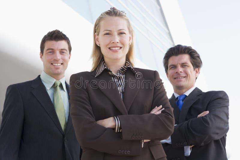 Três empresários que estão ao ar livre pelo edifício imagem de stock