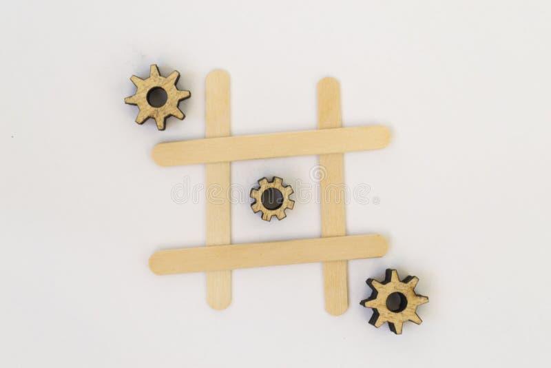 Três engrenagens de madeira da mentira do mecanismo em seguido em uma linha no jogo do dedo do pé do tac do tique, em uma grade e imagens de stock royalty free