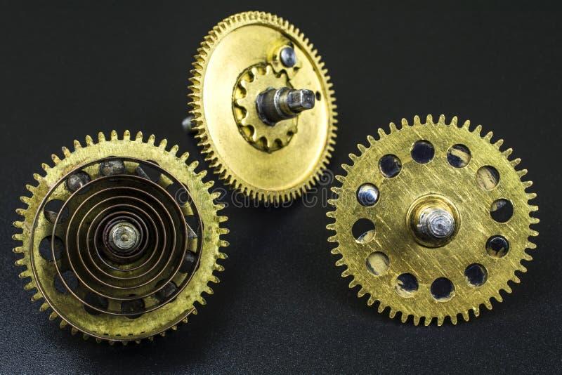 Três engrenagens feitas da mentira de bronze em um fundo preto imagem de stock royalty free