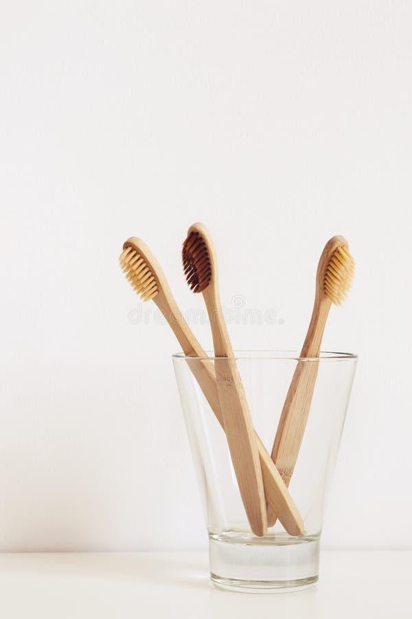 Três escovas de dentes de bambu com as cerdas naturais no vidro imagens de stock royalty free