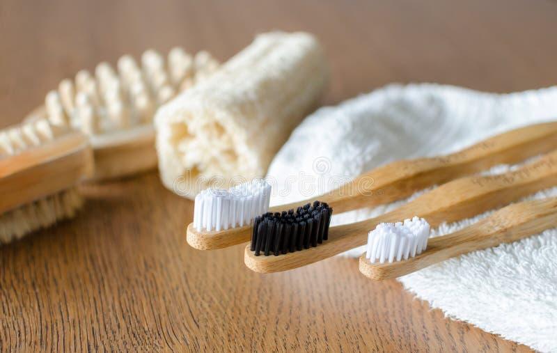 Três escovas de dentes de bambu com a bucha livre plástica natural de toalha e de eco, escovas de madeira no fundo fotos de stock royalty free