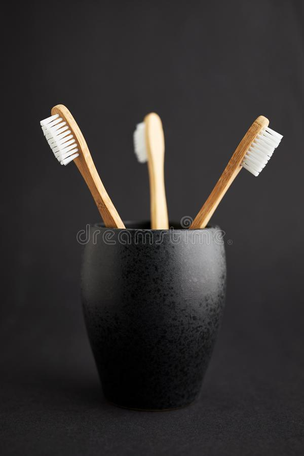 Três escovas de dentes de bambu em um vidro preto fotos de stock
