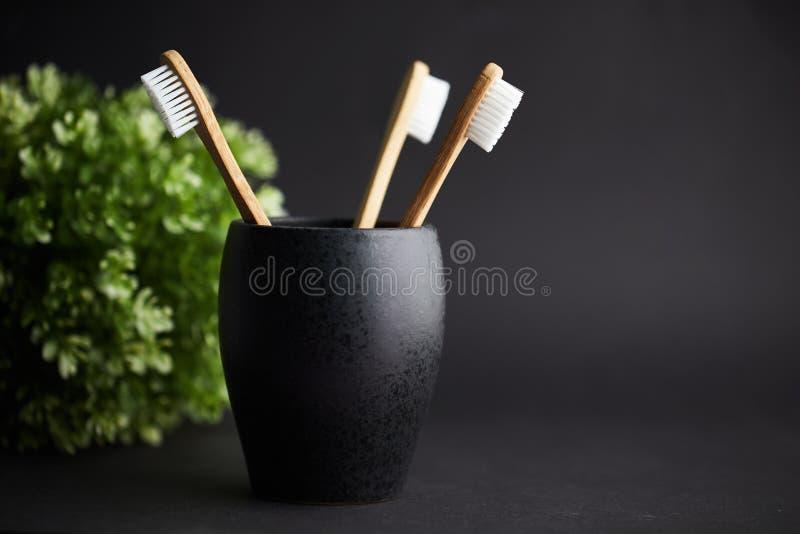 Três escovas de dentes de bambu em um vidro preto com espaço da cópia imagens de stock royalty free