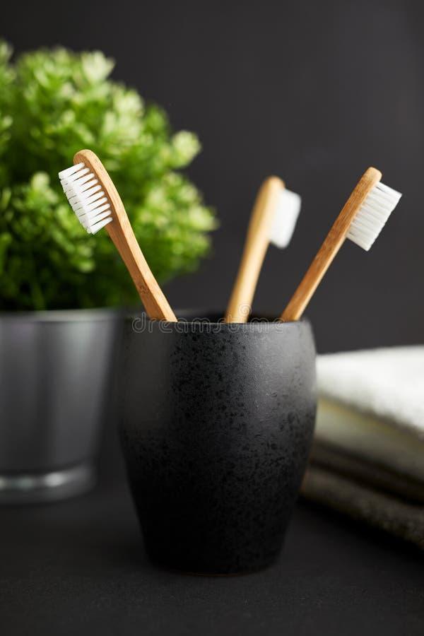 Três escovas de dentes de bambu em um vidro preto com planta em um fundo escuro imagem de stock