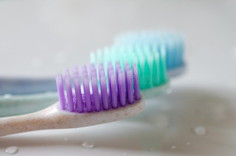Três escovas de dentes de cores diferentes no fundo branco fotografia de stock