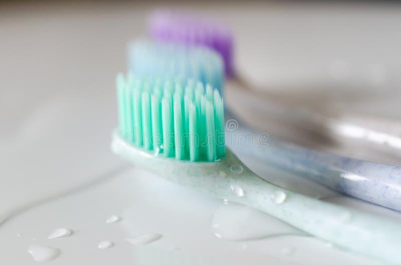 Três escovas de dentes de cores diferentes no fundo branco foto de stock royalty free