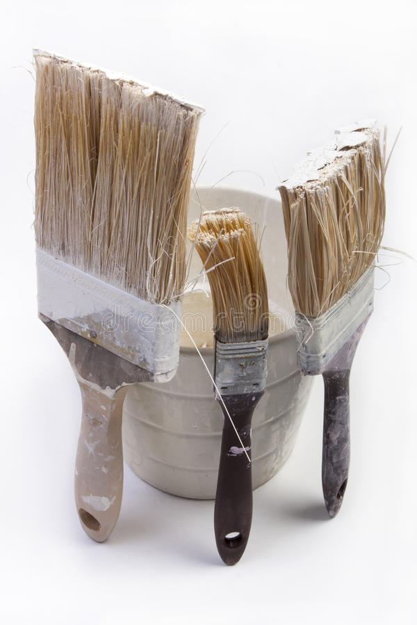 Três escovas velhas usadas e um frasco No backgorund branco imagem de stock