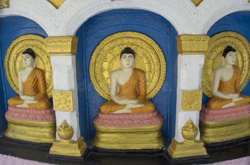Três estátuas budistas bonitas no altar no templo imagens de stock