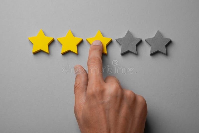 Três estrelas amarelas douradas fora de cinco Equipe o dedo dos pontos na estrela, põe a avaliação imagens de stock royalty free
