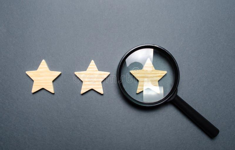Três estrelas e uma lupa em um fundo cinzento Autenticação da terceira estrela, fraude de avaliação Avaliação e estado do imagens de stock