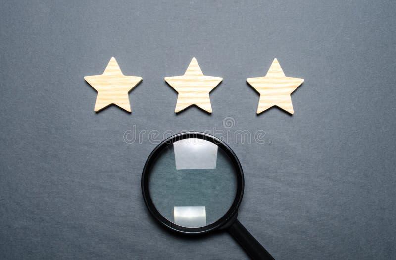 Três estrelas e uma lupa em um fundo cinzento Avaliação e estado do restaurante ou do hotel prestige De alta qualidade e imagens de stock royalty free