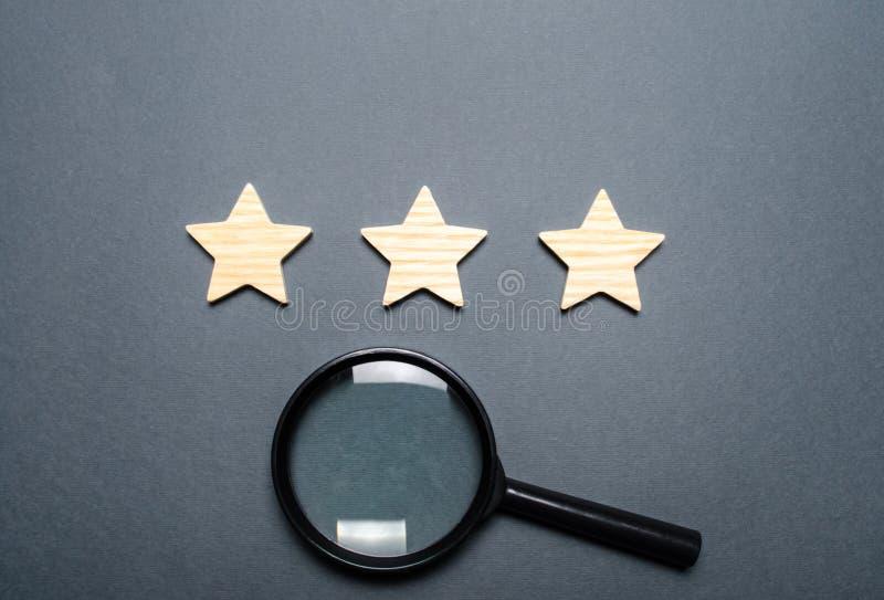 Três estrelas e uma lupa em um fundo escuro Avaliação e estado do restaurante ou do hotel prestige De alta qualidade fotografia de stock royalty free