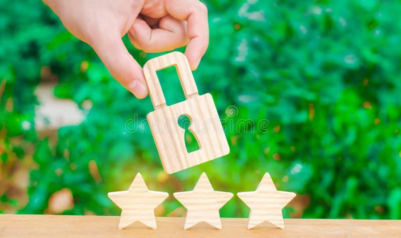 Três estrelas e uma mão que guarda um fechamento O conceito de alta qualidade e da proteção Consolidação dos resultados e das rea fotografia de stock royalty free