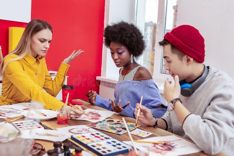 Três estudantes de arte que têm alguns argumentos ao trabalhar junto imagens de stock royalty free