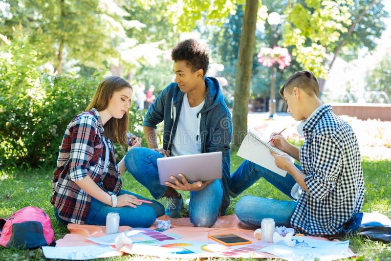 Três estudantes modernos que gastam sua pausa para o almoço no parque imagens de stock