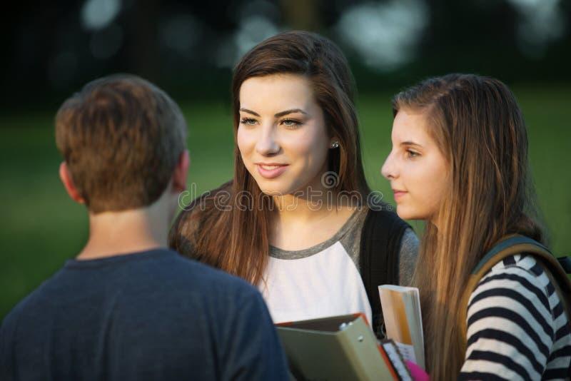 Três estudantes que falam fora imagem de stock royalty free