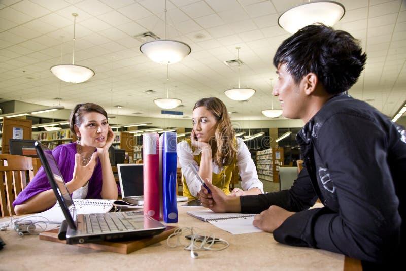 Três estudantes universitários que estudam junto imagens de stock
