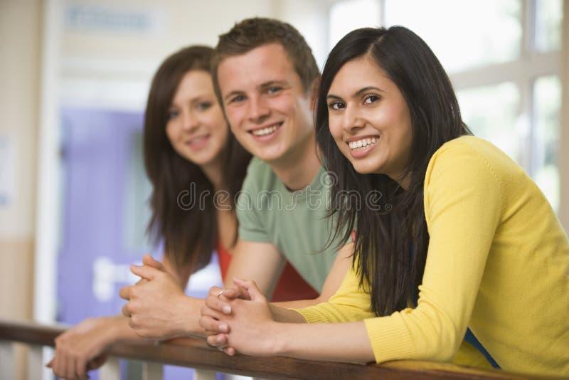 Três estudantes universitários que inclinam-se no corrimão fotografia de stock royalty free