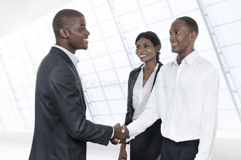 Três executivos africanos do aperto de mão imagens de stock royalty free