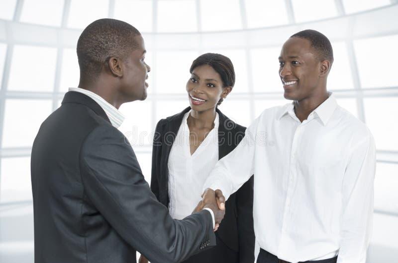 Três executivos africanos do aperto de mão fotografia de stock