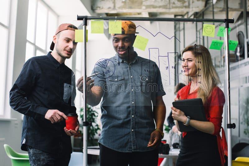Três executivos novos que encontram-se em notas de post-it do escritório e do uso para compartilhar da ideia Conceito da sess?o d foto de stock