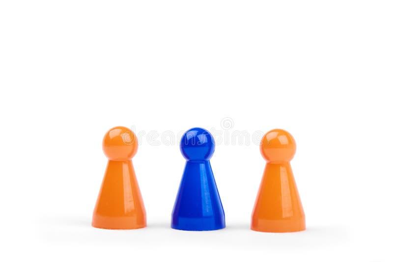 Três figuras plásticas de jogo Dois azul alaranjados e um diferentes, isolado no fundo branco imagem de stock
