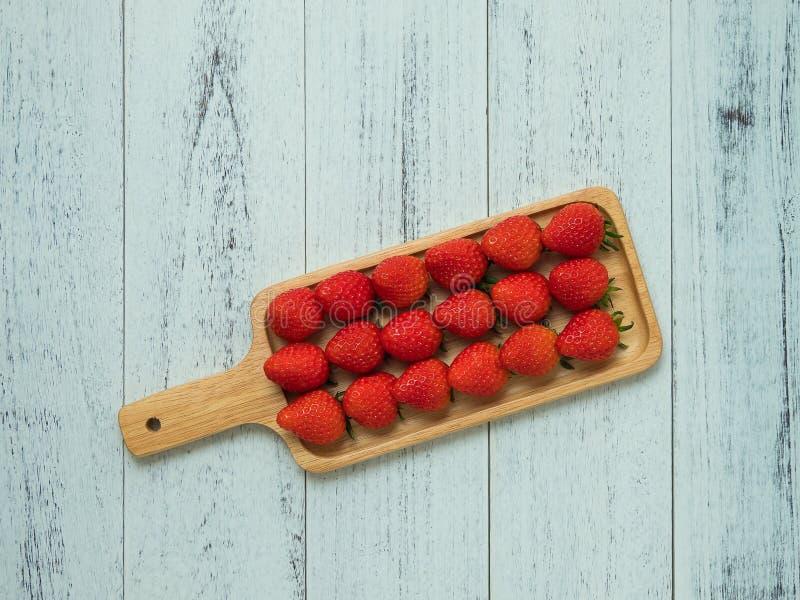 Três fileiras de morangos maduras suculentas em servir a placa no fundo de madeira branco, vista superior Sobremesas e tema saudá imagens de stock royalty free