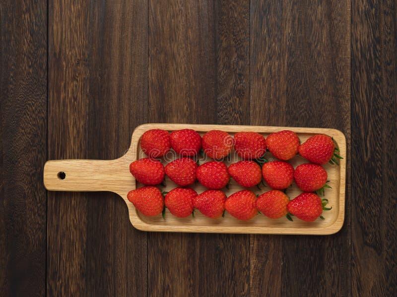 Três fileiras de morangos maduras suculentas em servir a placa no fundo de madeira marrom, vista superior Sobremesas e tema saudá imagem de stock royalty free