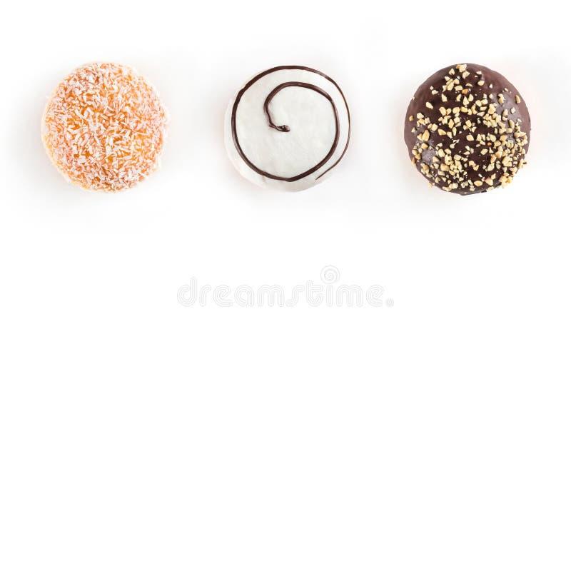 Três filhóses doces com o chocolate, as porcas, chocolate branco e cocos isolados no fundo branco imagem de stock royalty free