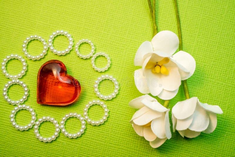 Três flor branca de papel em uma carcaça verde ao lado do coração de vidro vermelho, ofícios com cumprimentos do amor fotos de stock royalty free