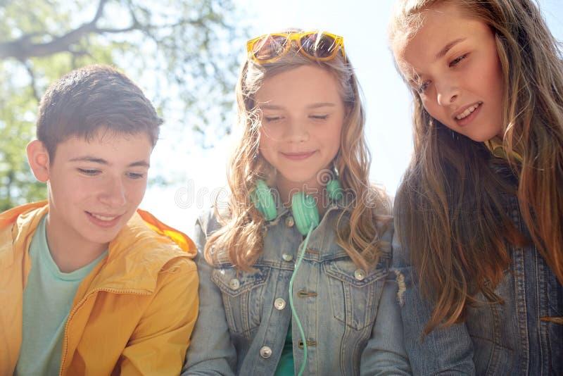 Três fones de ouvido adolescentes felizes dos amigos imagens de stock royalty free
