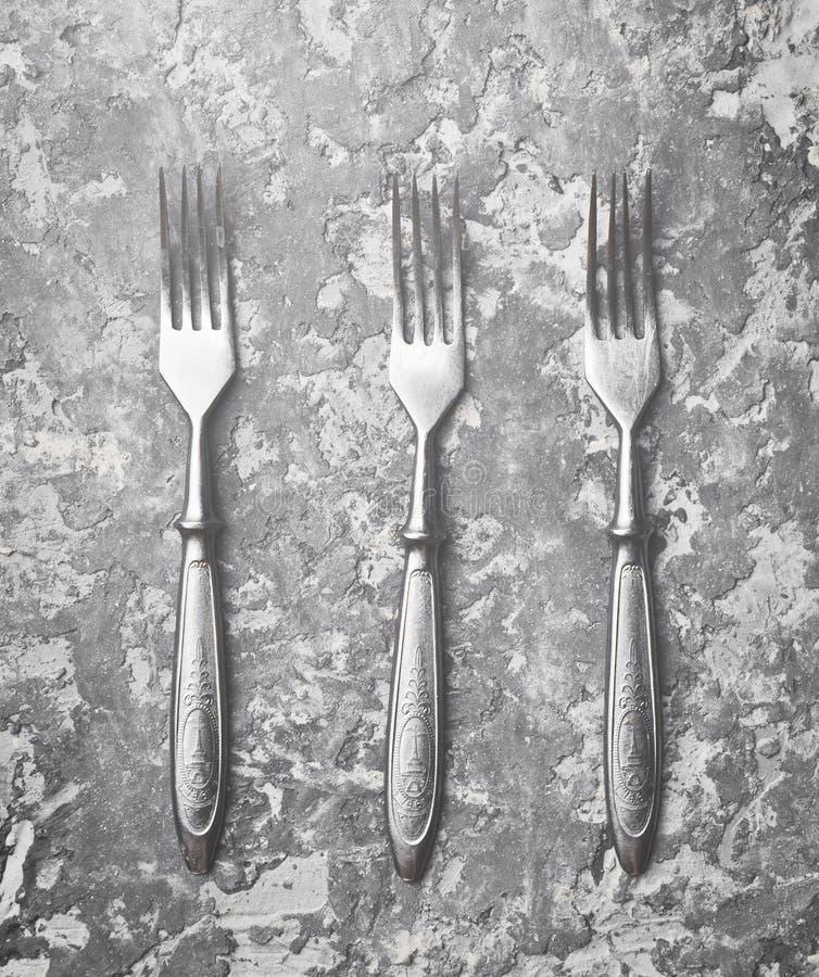Três forquilhas antigas em uma tabela concreta cinzenta Vista superior imagens de stock