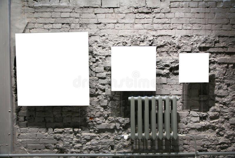 Três frames em branco na parede de tijolo cinzenta imagens de stock