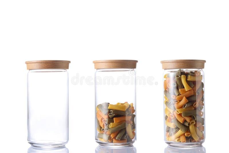 Três frasco de vidro, um vazio, um meio vazio e um completo da massa crua colorida isolada no fundo branco com trajeto de grampea fotos de stock royalty free