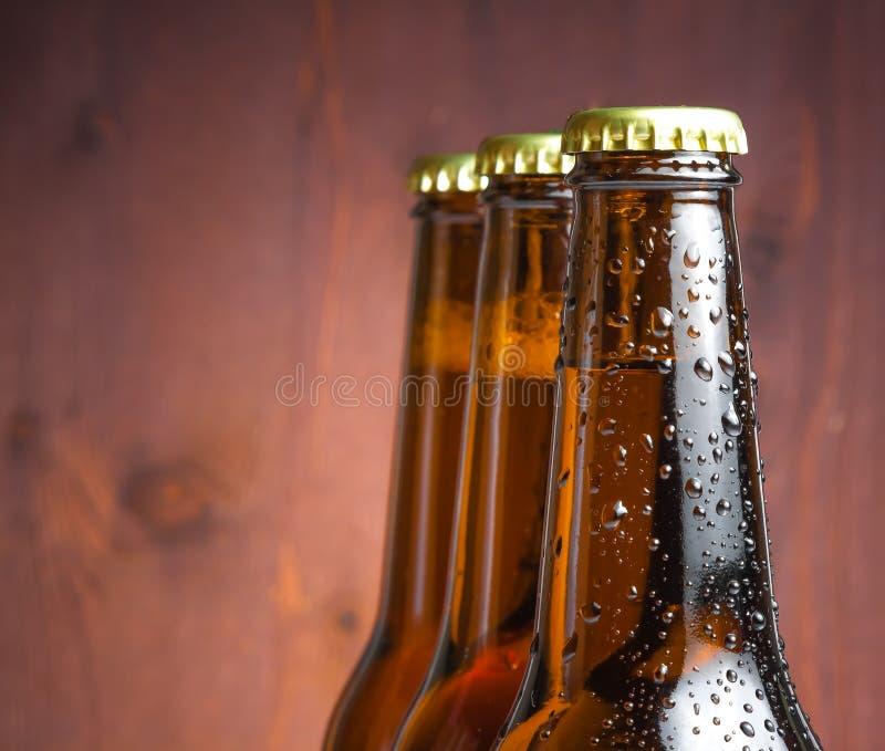 Três garrafas da cerveja fresca com gotas imagens de stock