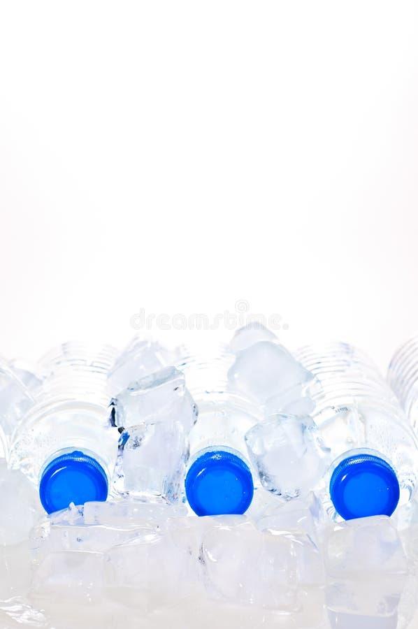 Três garrafas de água minerais no gelo imagem de stock