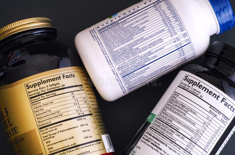 Três garrafas do suplemento dietético com etiquetas dos fatos do suplemento imagem de stock