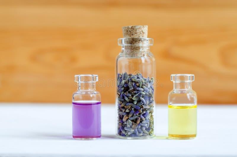 Três garrafas pequenas com os botões secos da alfazema, óleo essencial e perfume natural Ingredientes da aromaterapia e dos terma fotografia de stock royalty free