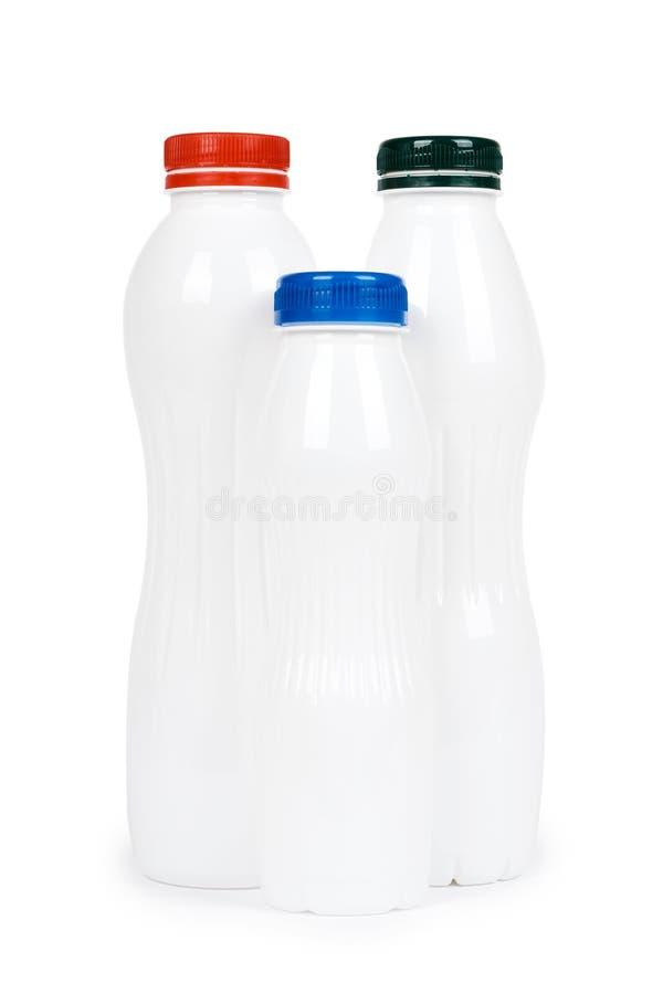 Três garrafas plásticas brancas com iogurte ou leite da bebida Isolado no fundo branco Molde da mercadoria do recipiente fotos de stock royalty free