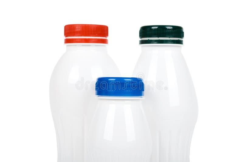 Três garrafas plásticas brancas com iogurte ou leite da bebida Isolado no fundo branco Molde da mercadoria do recipiente fotografia de stock
