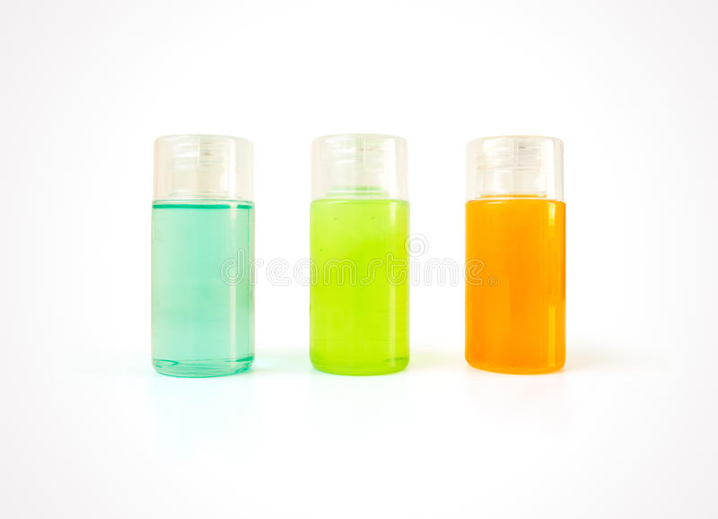 Três garrafas plásticas pequenas completamente de produtos cosméticos coloridos fotos de stock