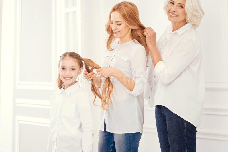 Três gerações de mulheres que fazem os penteados imagens de stock