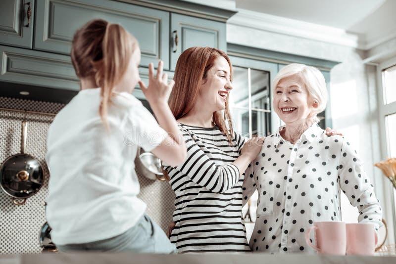 Três gerações de parentes que estão na cozinha e que olham felizes fotos de stock royalty free