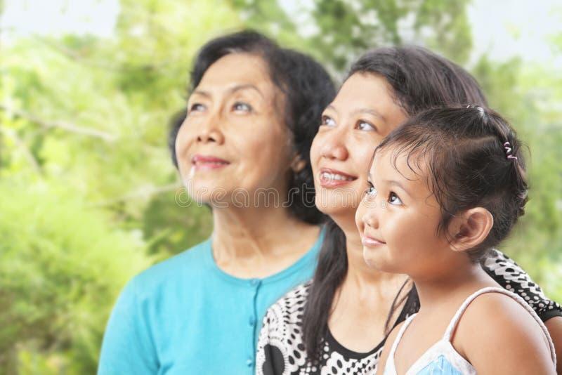 Três gerações fêmeas asiáticas que olham afastado imagem de stock