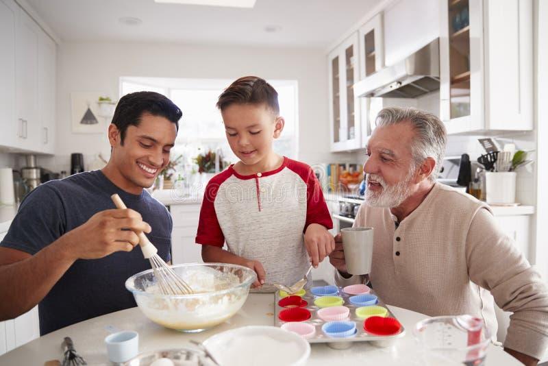 Três gerações masculinas de família que preparam bolos junto na tabela na cozinha, fim acima fotografia de stock royalty free