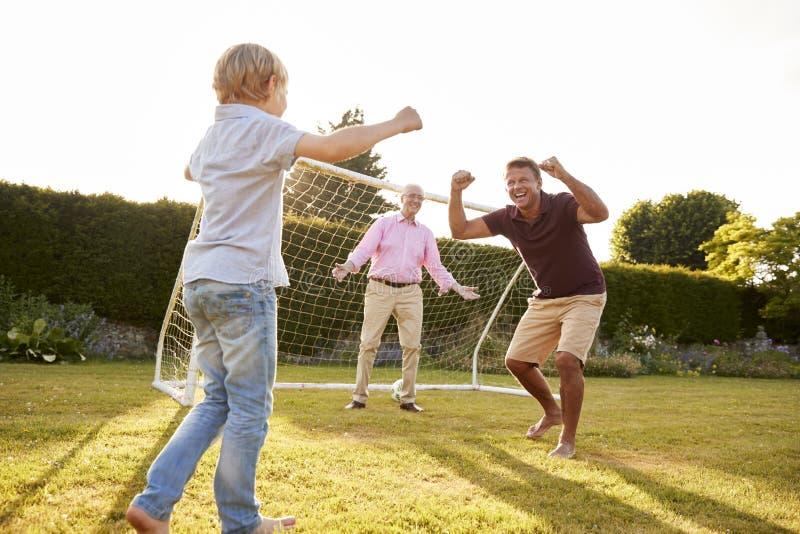 Três gerações masculinas de uma família que cheering no jardim foto de stock royalty free